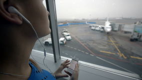 Woman listening to music by the window at airport. Woman listening to music using smart phone while looking out the window at airport stock footage