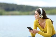 Free Woman Listening To Music With Headphones Looking Away Royalty Free Stock Image - 217693116