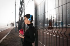Woman listening to music while working out and jogging outdoor Royalty Free Stock Image