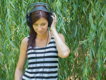 Woman listening to music. Young woman in t-shirt listening to music before willow tree Stock Images