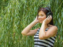 Woman listening to music. Young woman listening to music before willow plant Stock Photos