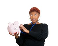 Woman listening to piggy bank Royalty Free Stock Photography