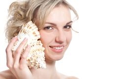 Woman is listening to the sea-shell Stock Image