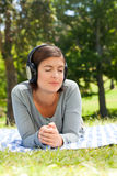 Woman listening to some music. In the park Royalty Free Stock Photo