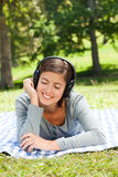 Woman listening to some music in the park. And smilling Royalty Free Stock Photo