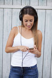 Woman listening wireless music with headphones from a smart phone Stock Photography