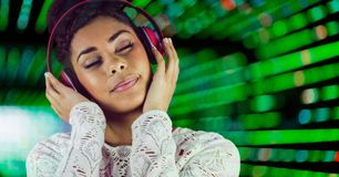 Woman listenning music with headphones with a green background Stock Photography