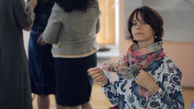 Woman listens carefully and ties beautiful scarf on neck at the same time. stock video footage
