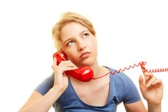 Woman listens to frustrated background music on hold. Young woman hears frustrated background music in a telephone waiting loop stock photos