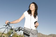 Woman Listens To MP3 Holding Handlebars On Mountain Bike Royalty Free Stock Image