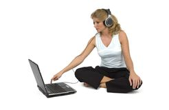 A woman listens to music. A woman listens to music on the laptop Royalty Free Stock Images