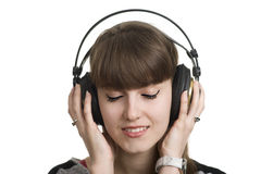 A woman listens to music and dreams. A woman listens to good music through headphones. Music bring her in a good mood Stock Photos