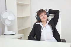Woman listens to music in ear-phones Stock Image
