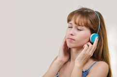 The woman listens to music in earphones Royalty Free Stock Images