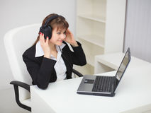 Woman listens to music by means of laptop Royalty Free Stock Image