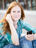 Woman Listens to Music on a Smartphone Stock Photo