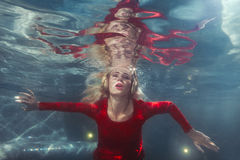 Woman listens to music underwater. Woman listens to music under the water in the pool Stock Photo