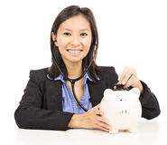 Woman listens to a piggy bank with a stethoscope. Asian woman listens to a piggy bank with a stethoscope isolated on withe background Royalty Free Stock Photography