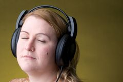 Woman listing to music. Women listing to music with her eye close Stock Image