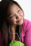 Woman listing to music. Young Asian woman listening to music on earphones, white studio background Stock Photo