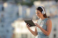 Woman litening to music browsing a tablet royalty free stock images