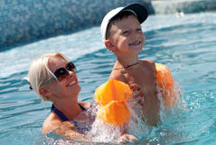 Woman and little boy bathes in pool. Smiling beautiful woman and little boy bathes in pool Stock Image