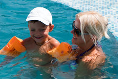 Woman and little boy bathes in pool. Smiling beautiful woman and little boy bathes in pool Stock Photos