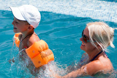 Woman and little boy bathes in pool. Smiling beautiful woman and little boy bathes in pool Stock Photography