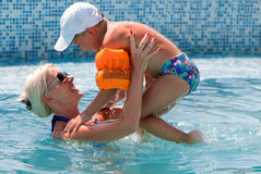 Woman and little boy bathes in pool Stock Image