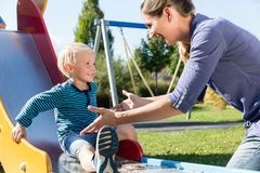 Woman and little boy chuting down slide at playground Stock Image