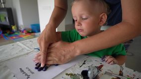 Woman with little boy making palm hand print stamp with gouache paint stock video footage