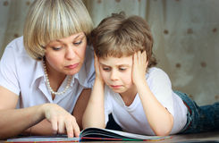 Woman and little boy reading book Stock Images