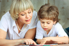 Woman and little boy reading book Stock Image