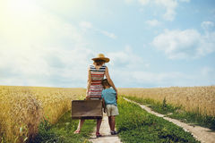 Woman and little boy standing in middle of country Stock Images
