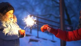 Woman and the little boys burning sparklers in the street. Happy new year stock video