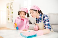 Woman and a little child girl wiped. Young asian women and a little child girl wiped the dusting table in the living room at home. Mother and daughter do the royalty free stock photos