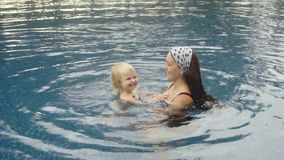 Woman and little cute girl playing in pool stock video footage