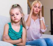 Woman and little daughter having quarrel. Upset young blonde women and her little daughter having quarrel indoors Royalty Free Stock Photo