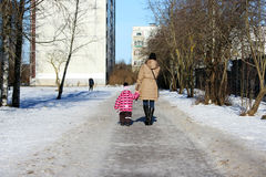Woman with little daughter walking along the road near the house. Royalty Free Stock Images