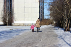 Woman with little daughter walking along the road near the house. Stock Images