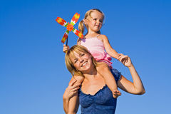 Woman with little girl against summer sky Royalty Free Stock Images