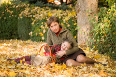 Woman and little girl in autumn park with apple Royalty Free Stock Photo