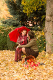Woman and little girl in autumn park with apple basket Stock Photos