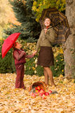 Woman and little girl in autumn park with apple basket Royalty Free Stock Photography