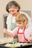 Woman and little girl baking cupcakes together Stock Photography