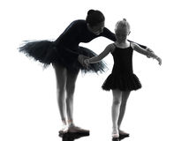 Woman and little girl ballerina ballet dancer dancing silhouett. Woman and little girl ballerina ballet dancer dancing in silhouette on white background royalty free stock image