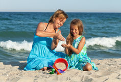Woman and little girl on the beach Stock Photo
