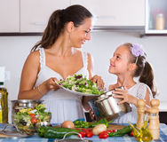 Woman and little girl cooking vegetables. Portrait of mother and little girl cooking vegetables Stock Image
