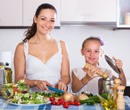 Woman and little girl cooking vegetables. Portrait of positive women and little girl cooking vegetables Stock Images