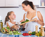 Woman and little girl cooking vegetables. Portrait of positive women and girl 7 years old cooking vegetables Stock Photo